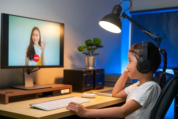 Portrait d'une fille asiatique heureuse à l'aide de la téléconférence vidéo pour étudier en ligne avec son professeur à la maison.