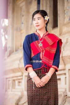 Portrait de fille asiatique avec la robe traditionnelle locale thaïlandaise célèbre dans la campagne de la thaïlande