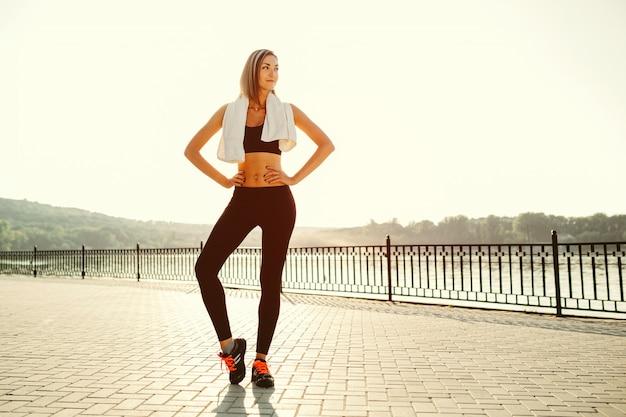 Portrait d'une fille athlétique. beau modèle de fitness sport jeune se prépare pour le jogging dans le parc de la ville.