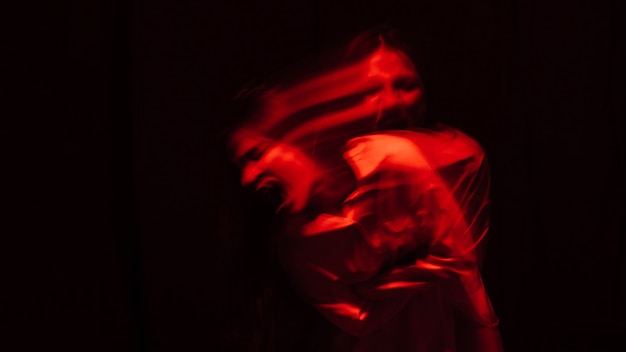 Portrait d'une fille atteinte de schizophrénie et de troubles mentaux dans une chemise blanche avec lumière rouge sur fond noir