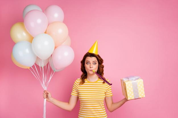 Portrait de fille aux cheveux ondulés tenant dans les mains des boules d'air s'amusant festive