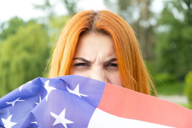 Portrait de fille aux cheveux rouges en colère cachant son visage derrière le drapeau national des usa.
