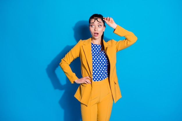 Portrait d'une fille de banquier étonnée, des lunettes tactiles regardent un espace de copie impressionné par une nouveauté inattendue incroyable isolée sur fond de couleur bleue