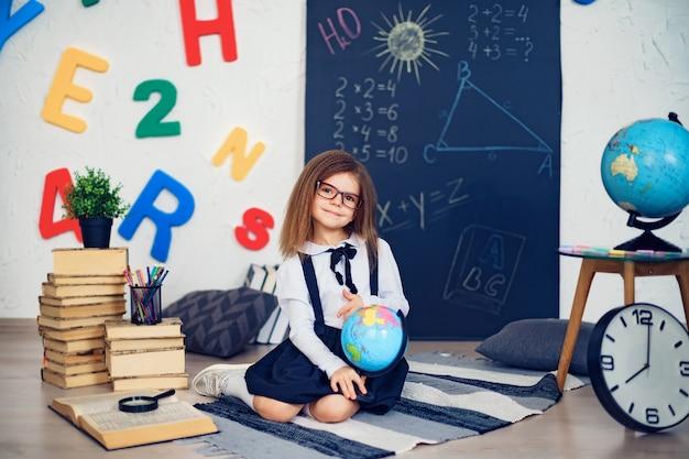 Portrait d'une fille de belle jeune écolière tenant le globe, assis sur le sol sur le tapis.