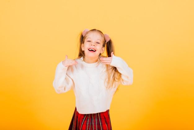 Portrait d'une fille belle, joyeuse et confiante isolée sur jaune