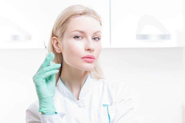 Portrait d'une fille blonde dans une blouse médicale avec une seringue dans ses mains. publicité du centre médical. technique mixte
