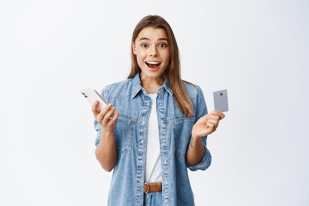 Portrait d'une fille blonde excitée faisant ses achats en ligne sur un smartphone, tenant une carte de crédit et souriante étonnée, debout sur un mur blanc