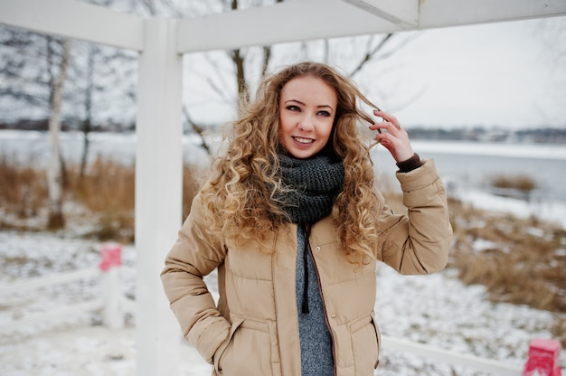 Portrait d'une fille blonde frisée à la journée d'hiver.