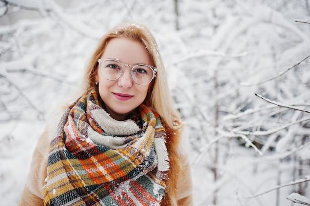 Portrait de fille blonde à lunettes, manteau de fourrure rouge et foulard au jour de l'hiver.