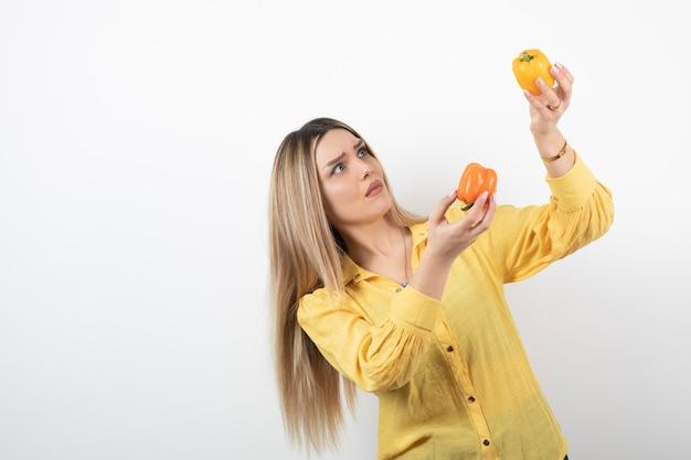 Portrait d'une fille blonde regardant des poivrons colorés sur un mur blanc.