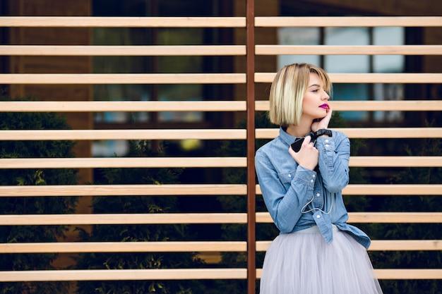 Un portrait d'une fille blonde rêveuse avec des lèvres rose vif et un maquillage nude, écouter de la musique sur un smartphone avec des arrières en bois rayé