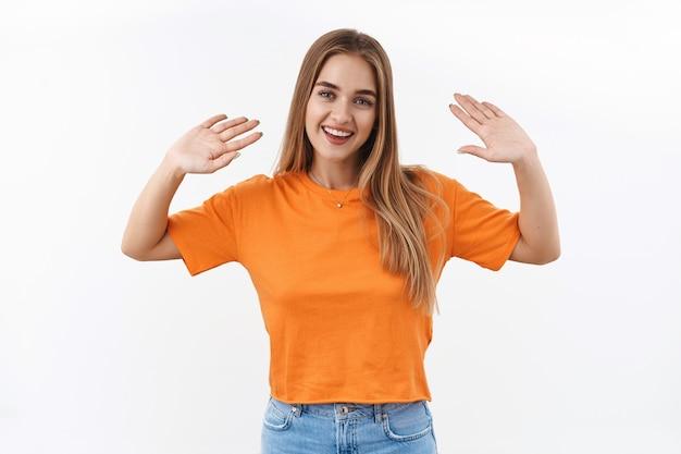 Portrait d'une fille blonde souriante et joyeuse, employée de bar au café, disant au revoir ou bonjour aux chers invités, salutation informelle, agitant les mains dans un geste de salut