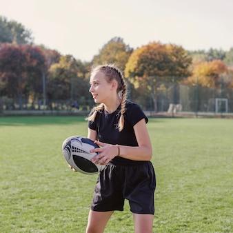 Portrait de fille blonde tenant un ballon de rugby