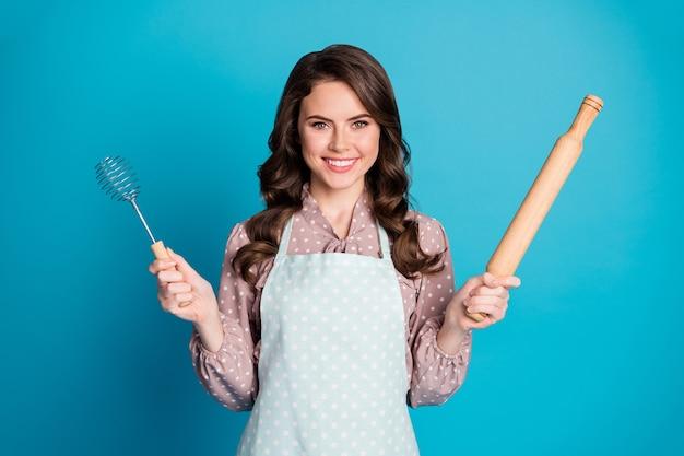 Portrait de fille de bonne gaie positive tenir des ustensiles de cuisine au rouleau à pâtisserie préparer le repas du soir délicieux dessert savoureux porter des vêtements à pois isolé fond de couleur bleu