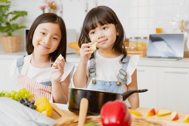 Portrait fille en bonne santé childs heureux de jouer ensemble dans la cuisine en mangeant des pommes