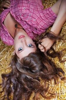 Portrait d'une fille brune aux cheveux longs sur la botte de foin
