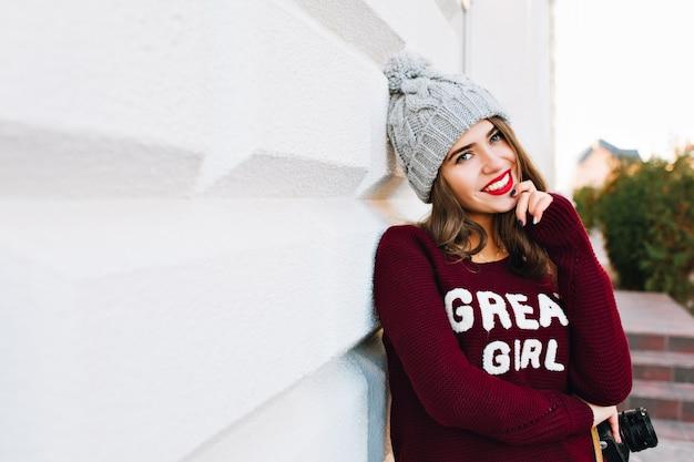 Portrait fille brune aux cheveux longs en pull d'hiver et bonnet tricoté sur mur gris sur rue. elle sourit.