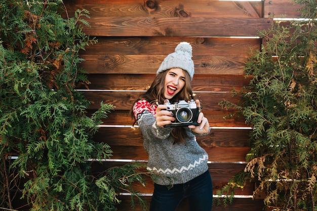 Portrait fille brune aux lèvres rouges et cheveux longs en vêtements d'hiver s'amusant avec appareil photo sur bois.