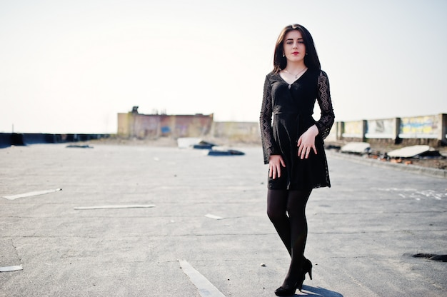Portrait fille brune aux lèvres rouges vêtue d'une robe noire, de collants et de chaussures à talons posée sur le toit