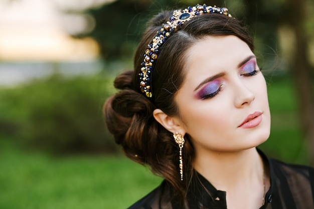 Portrait de fille brune à la mode avec un magnifique maquillage lumineux. les yeux sont fermés. bijoux coûteux et élégants, un bandeau, un cerceau avec des pierres précieuses, des boucles d'oreilles en diamant.