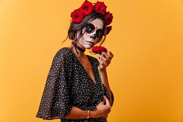 Portrait de fille calme aux cheveux noirs en couronne de fleurs rouges. femme avec masque squelette appréciant le parfum des fleurs.