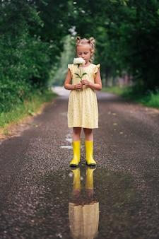 Portrait de fille caucasienne de 6 ans en robe jaune et bottes de pluie debout dans le parc tenant une fleur de pivoine