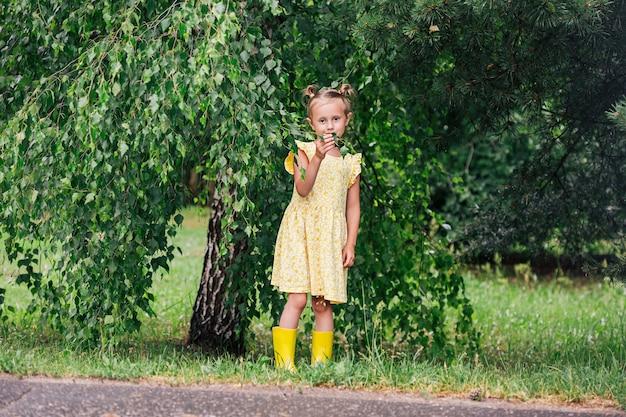 Portrait de fille caucasienne de 6 ans en robe jaune et bottes de pluie debout dans le parc