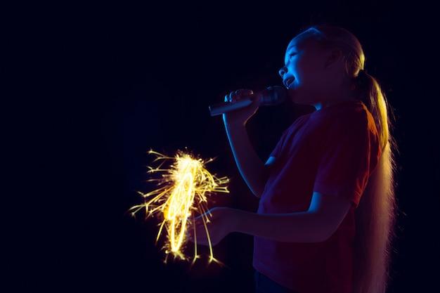Portrait d'une fille caucasienne isolée sur fond de studio sombre à la lumière du néon