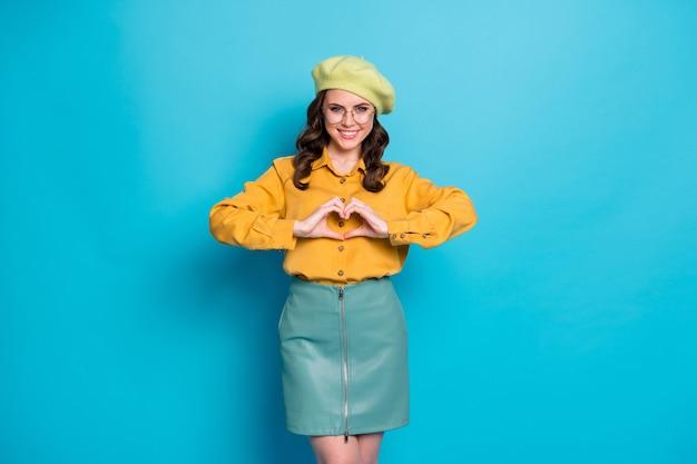 Portrait d'une fille charmante et passionnée positive, symbole de l'amour, figure en forme de coeur, faire porter aux doigts des vêtements jaunes de bonne apparence isolés sur fond de couleur bleu