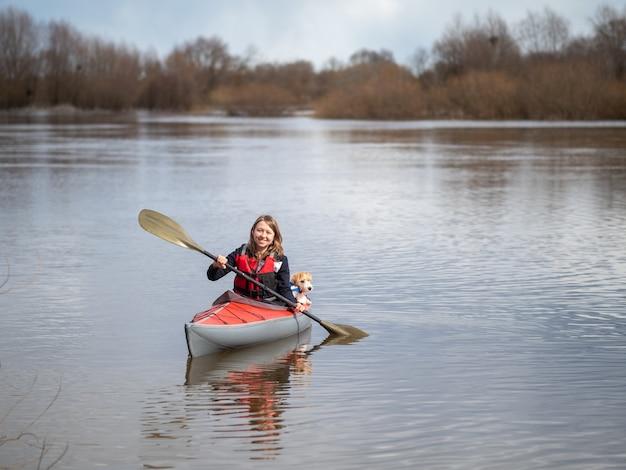 Portrait d'une fille et d'un chien de race jack russell terrier sur un kayak rouge.