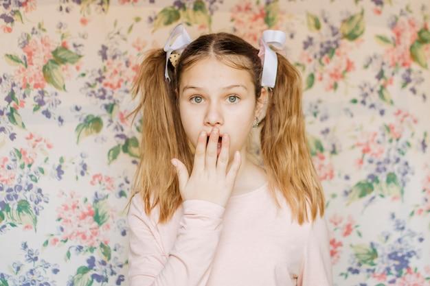 Portrait d'une fille choquée avec la main sur la bouche