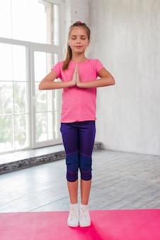Portrait, fille, debout, exercice, méditation, tapis