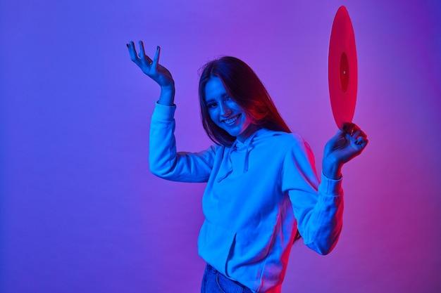 Portrait de fille disco sourit et tenant un vinyle rétro avec de la musique des années 80 sur fond clair néon.