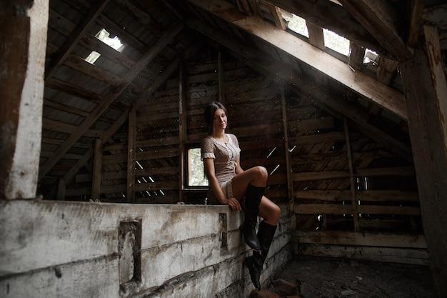 Portrait d'une fille du village dans le grenier, fumant une cigarette et soufflant de la fumée