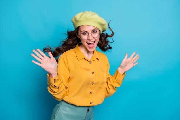 Portrait d'une fille émerveillée énergique et excitée profiter du vent de l'air voler sa coupe de cheveux porter des vêtements jaunes chapeaux isolés sur fond de couleur bleu