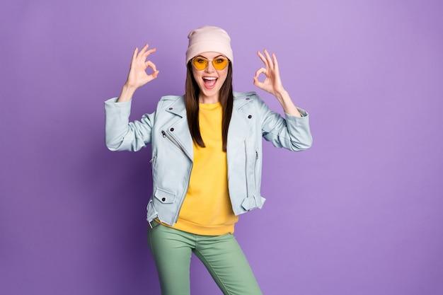 Portrait d'une fille énergique et folle profitez d'excellentes annonces promotionnelles recommandez de choisir de décider de montrer le signe d'accord porter un pantalon vert jaune isolé sur fond de couleur violet