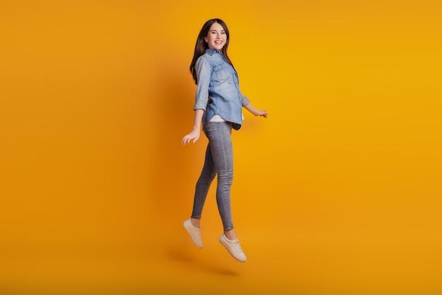 Portrait d'une fille énergique joyeuse active sautant isolée sur fond jaune