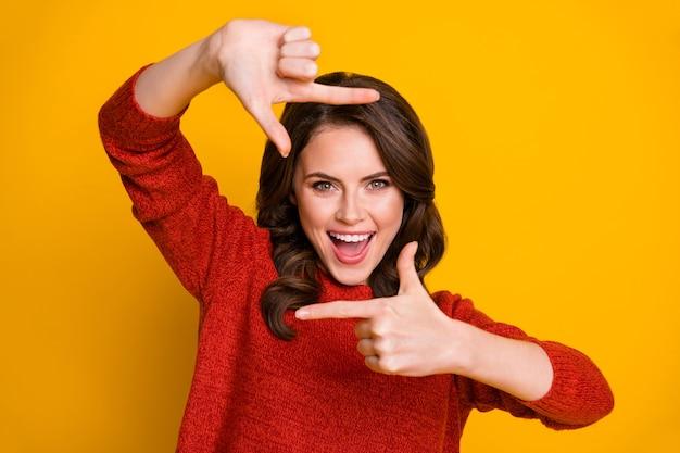 Portrait d'une fille énergique et joyeuse qui aime imaginer faire un pull photo avec un doigt isolé sur un fond de couleur brillante