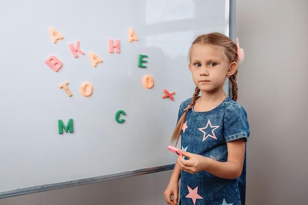 Portrait d'une fille enfant assez perplexe debout en face d'un grand tableau blanc sur lequel les lettres de l'alphabet sont dispersées de manière chaotique. concept de connaissances photo avec bruit