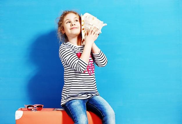 Portrait de fille enfant blonde écouter un coquillage sur le mur bleu. concept de vacances d'été.