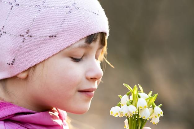 Portrait de fille enfant heureux holding bouquet de fleurs de perce-neige au début du printemps à l'extérieur.
