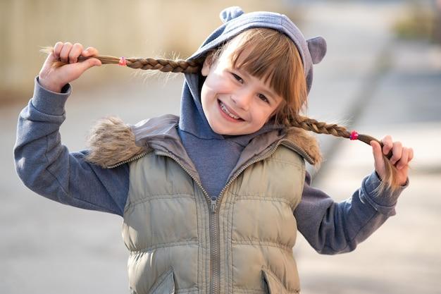 Portrait de fille enfant heureux avec des tresses de cheveux dans des vêtements chauds en automne à l'extérieur.