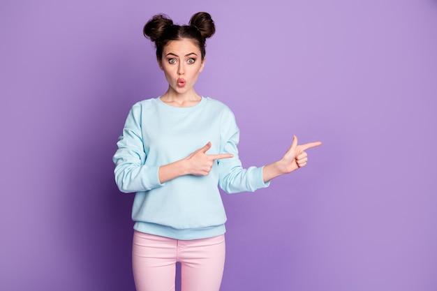 Portrait d'une fille étonnée, promoteur du millénaire, pointer l'index copyspace présente une promotion publicitaire incroyable porter un pantalon à la mode élégant isolé sur fond de couleur violet