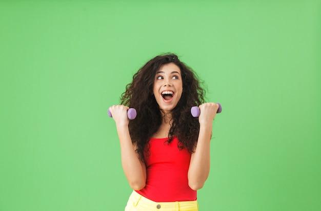 Portrait d'une fille européenne portant des vêtements d'été faisant du sport et soulevant des poids contre un mur vert