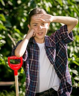 Portrait de fille fatiguée s'appuyant sur une pelle après le travail au jardin