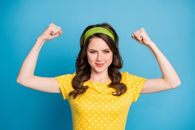 Portrait d'une fille fière et confiante lui montrer de fortes mains de biceps isolées sur fond de couleur bleu
