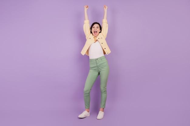 Portrait d'une fille folle étonnée réaction joyeuse bouche ouverte lever les mains sur fond violet