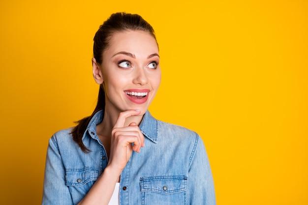 Portrait d'une fille folle gaie et positive regarde le copyspace toucher le menton à la main pense que les pensées ont impressionné une idée incroyable porter une chemise en jean isolée sur un fond de couleur vive
