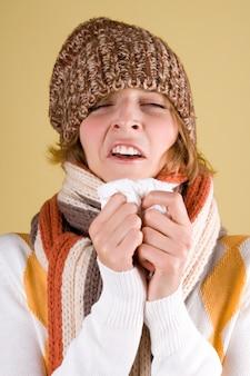Portrait d'une fille froide éternue avec un mouchoir et un thermomètre sur fond jaune