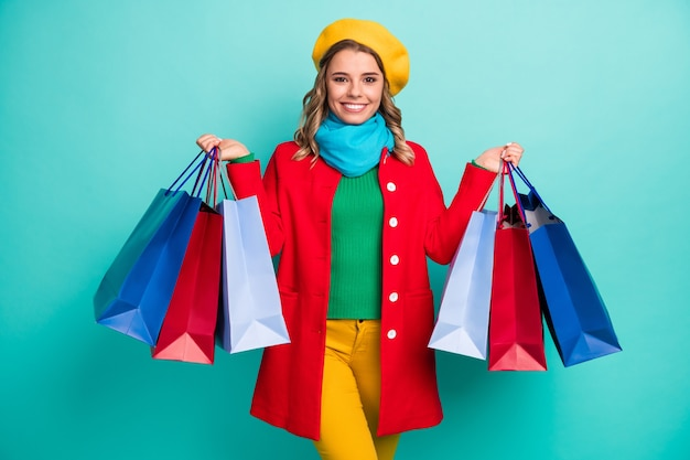 Portrait d'une fille gaie positive ayant un voyage de voyage profiter du shopping tenir de nombreux sacs porter un pantalon pull rouge bleu jaune isolé sur fond de couleur turquoise